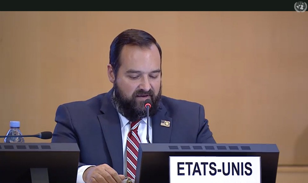 A screenshot from a video stream of the United Nation's universal periodic review of the United States. It features a man with dark hair and a dark beard, wearing a blue suit jacket and a red and white striped tie speaking into a microphone.